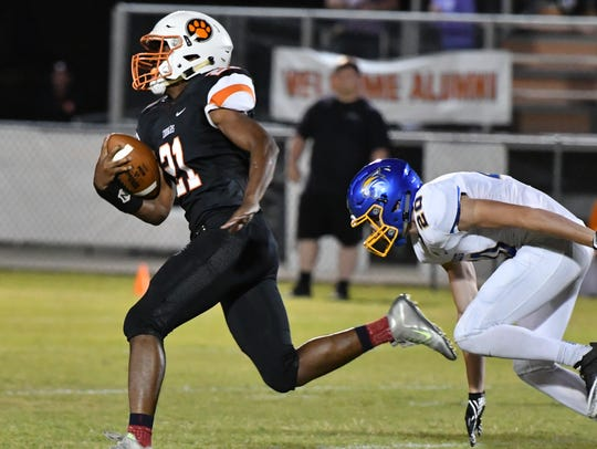 MTCS' Kemari McGowan runs away from DCA defenders during a 60-35 win Sept. 29.