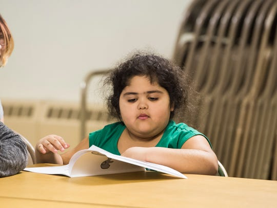 "Nayesha Lopez, 5, flips through pages of ""The Too Small Elephant"" by author Christine Callahan during a Girl Scout meeting at St. Paul's United Church of Christ in New Oxford Borough."