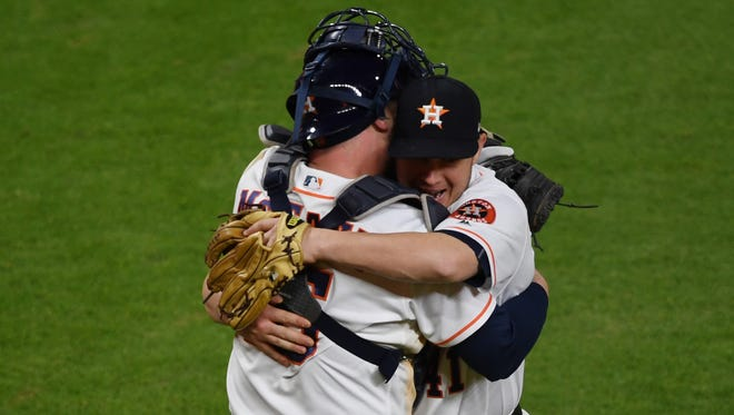 Astros pitcher Brad Peacock and catcher Brian McCann hug after defeating the Dodgers in Game 3.
