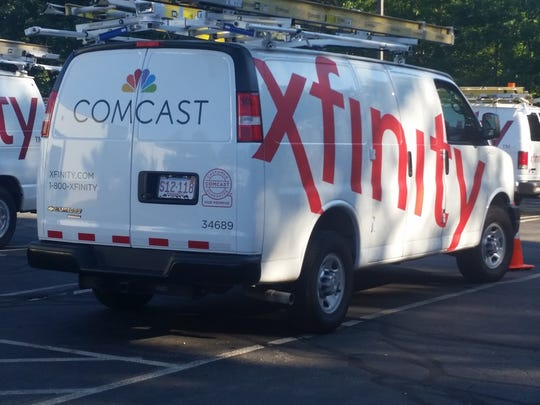 In this Sept. 17, 2015, photo, Comcast trucks are parked in a lot in the company's Westford, Mass. operations center.