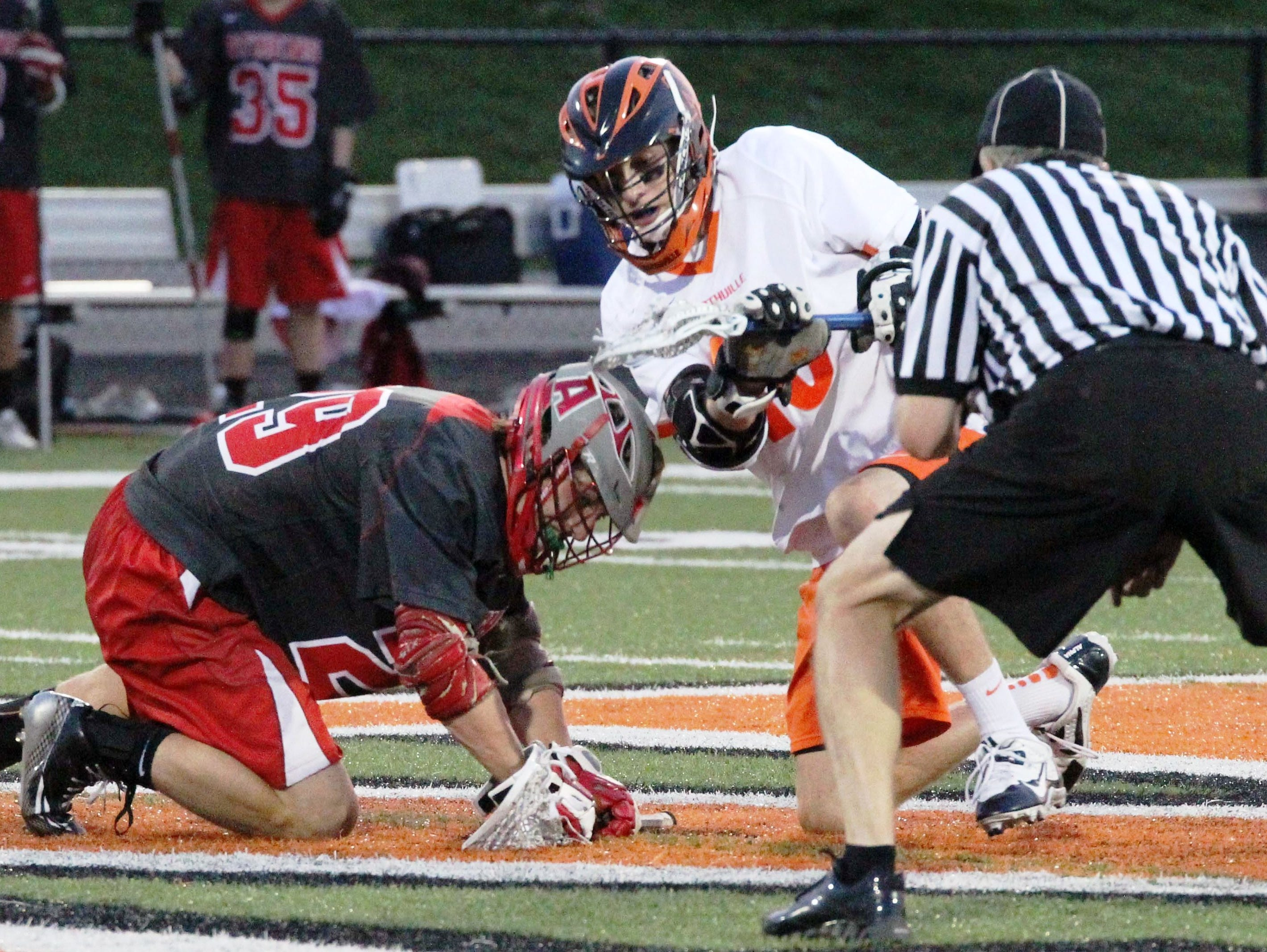 Northville senior David Morrissey (middle) wins the face-off in Thursday's win over Troy Athens.