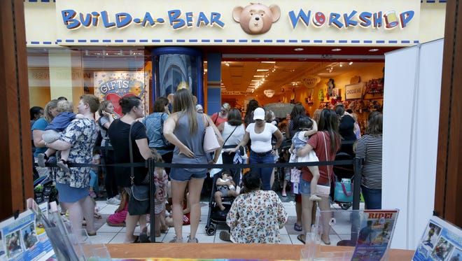Customers wait in line to enter Build-A-Bear Workshop at Eastview Mall.