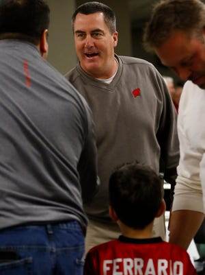 Badgers football Paul Chryst gets a handshake greeting by former Badgers and Packers player Bill Ferrario Thursday night at Dale's Weston Lane.