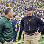 "Mark Dantonio, left, and U-M's Jim Harbaugh. Dantonio says satellite camps ""takes away from us doing opponent studies. It takes away from us critiquing ourselves."""