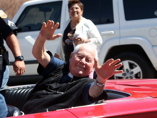 Father Harold Rahm waves from the back of a classic convertible during a parade in his honor in May 2015 in South El Paso.