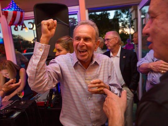 Bill Barnett, center, celebrates election results showing
