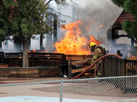 An Alamogordo firefighter works to extinguish the fire Friday at Kids Kingdom. Firefighters responded to the fire around 8:51 a.m Friday.