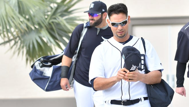 Tigers pitcher Anibal Sanchez bends the bill of his hat on the way to the field.