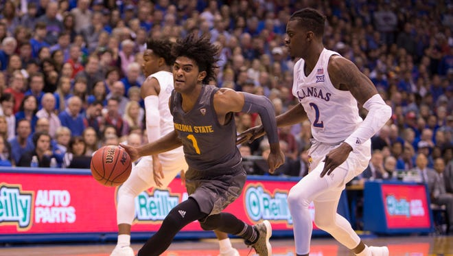 ASU freshman guard Remy Martin drives past Kansas guard Lagerald Vick during Sunday's game in Lawrence, Kan.