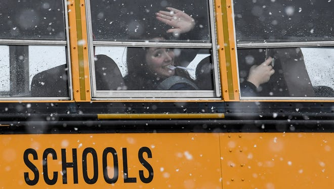 A Walhalla High School student waves inside a passing school bus after early dismissal on Friday.