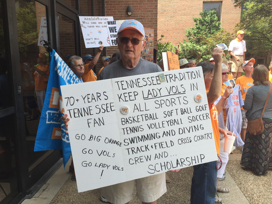 Tennessee fan Bob Roney, of Knoxville, holds a sign at Thursday's protest outside the university's annual board of trustees meeting.
