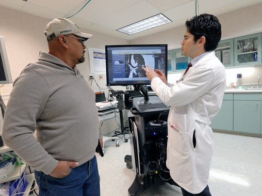 "Dr. Hector Payan shows his patient Cruz Mayer a new machine, which was used on him to help the detection and treatment of lung cancer. The Covidien superDimension Navigation System gives doctors turn-by-turn directions through the lungs to find abnormalities, which were previously detected by CAT scans. Mayer's ""spot"" was determined to not be cancer."