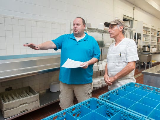 Manager Charles Martin, left, gives new employee Bobby