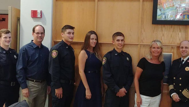 Three new members of the South Lyon fire Department were recently sworn in with family members pining on their badges. Shown are Dan Laitinen and his father Pete (left), Cain McGowan and his mother Stacey, Austin Dziurgot and his mother Erin and Fire Chief Mike Kennedy.