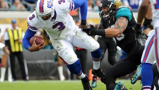 Dec 15, 2013; Jacksonville, FL, USA; Buffalo Bills quarterback EJ Manuel (3) runs the ball for a touchdown past Jacksonville Jaguars defensive end Jason Babin (58) during the first half at EverBank Field. Mandatory Credit: Melina Vastola-USA TODAY Sports