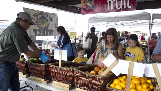 Shoppers pick out fruit at a produce tent at the Old Town Farmers Market in Scottsdale. Shoppers pick out fruit at a produce tent at the Old Town Farmers Market in Scottsdale.
