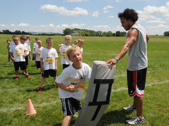 Riley Brenner hits the bag during a drill with coach AJ Hollanquest watching during the YMCA Youth Football camp held at the 20th Ave YMCA.