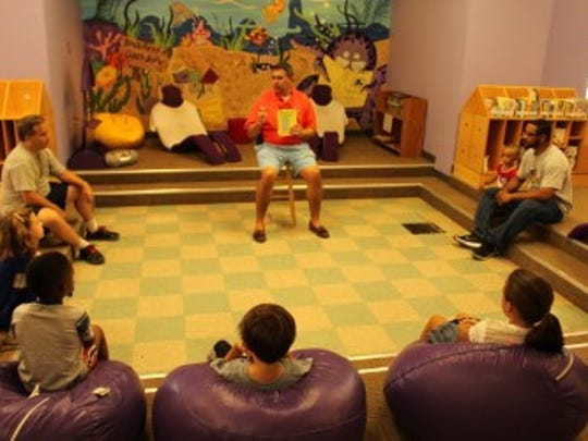 Matt Hall reads a book for boys and girls at the monthly