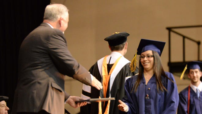 Corban University student Mariana Medina accepts her diploma during the school's commencement ceremony on Saturday.