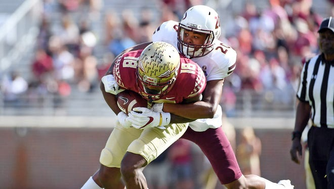 ULM cornerback Kenderick Marbles (20) tries to bring down Florida State wide receiver Auden Tate (1) during the first half at Doak Campbell Stadium.