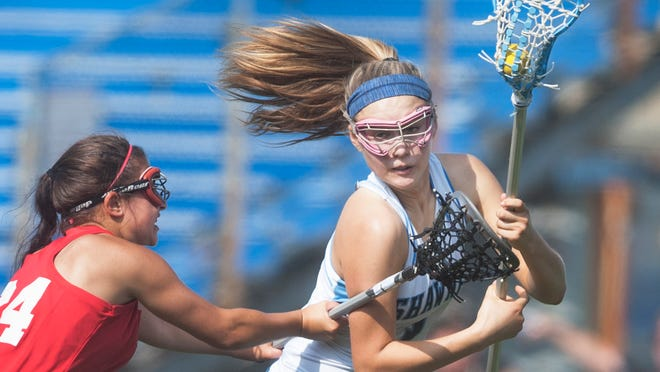 Shawnee's Liza Barr, right, controls the ball as she is checked by Washington Township's Lana Paulo during the second half of Tuesday's girls' lacrosse playoff game.