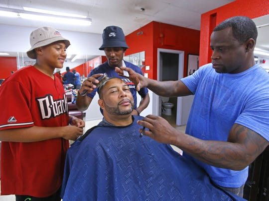 Getting a haircut from barber Kelvin Kimble is a family affair for Reggie Steele and his sons Ira, (left) and Isaac Steele, Saturday, June 6, 2015, at Liberty Barber Shop in El Mirage.