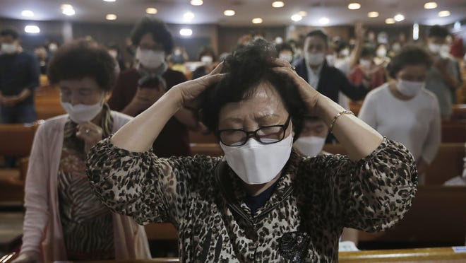 A Christian wearing a face mask to help protect against the spread of the new coronavirus prays during a service at the Yoido Full Gospel Church in Seoul, South Korea, Sunday, May 31, 2020.