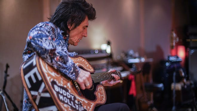 Ronnie Wood gets in some practice on a gift from the Buddy Holly Educational Foundation.
