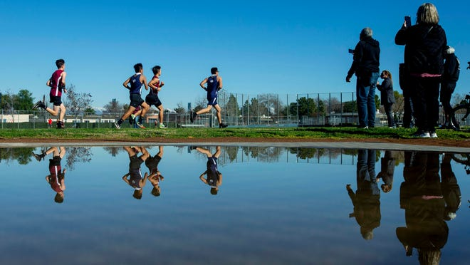 Ramona and Arlington boys compete in a River Valley League dual meet as school staffs and some family members are allowed to watch from a distance at Ramona High in Riverside, Calif., on Jan. 30.