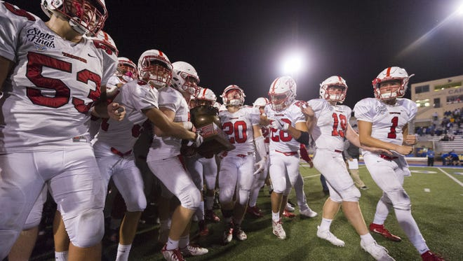 The Center Grove players celebrate with the trophy after winning an IHSAA high school football game at Carmel High School, Friday, September 1, 2017. Center Grove won the Copper Kettle game, 31-10.