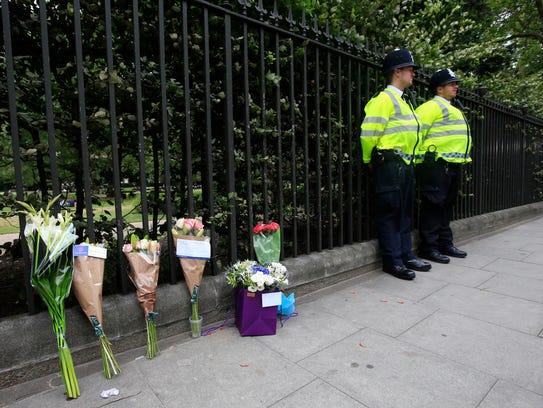 Floral tributes rest against railings Thursday Aug.