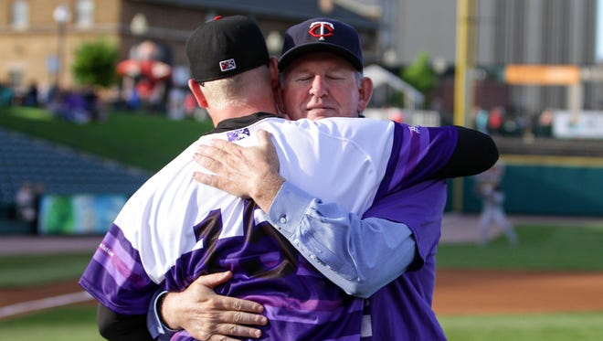 Red Wings pitcher Logan Darnell and his father, Rob, embrace after the ceremonial first pitch on June 19, 2015. The Red Wings wore special jerseys for Alzheimer's awareness night, a fundraiser for the Alzheimer's Association that was organized by Darnell. His mother, Caye, suffers from the disease.