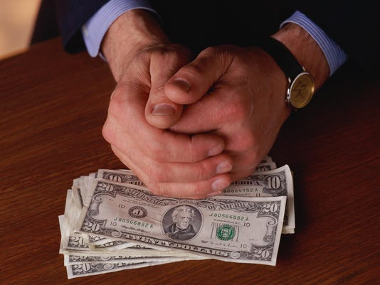 Man's clasped hands resting on stack of US $20 bills