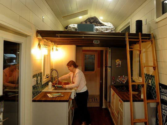 Tiffany Israel washes dishes inside her tiny house at an Oxnard RV park last year.