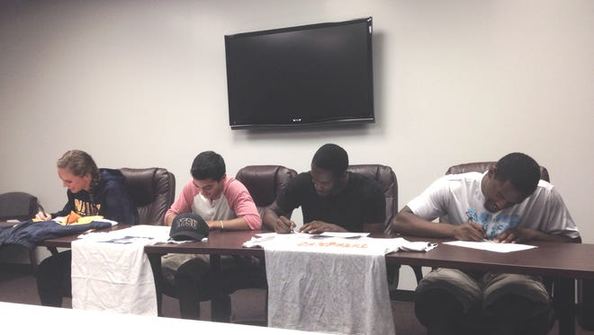 Asheville High seniors (from left to right) Pia Mackie, David Perez, Nate Tyson and Noah Tyson signed with college track programs on Tuesday morning.