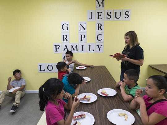 Jennifer Reeder reads to the students during snack time on Thursday, April 20, 2017. The Nehemiah Project serves at risk kids through a Christ based after school program and distributes food and clothing.