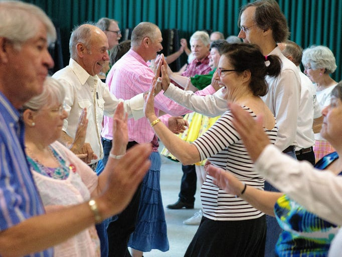 Dancers swing around to the directions of the caller at the Ocean Waves Square Dance Club's Blow Out at the Robert A Lee Rec Center in Iowa City on Sunday, July 13, 2014.