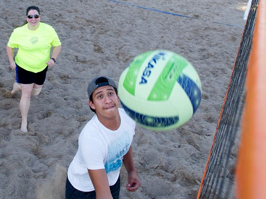 Javier Ortega digs the ball out of the net as his teammate Raena Cota moves in behind him to play the ball during a pickup sand volleyball game at Meerscheidt Recreation Center.