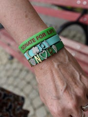 Robin Buskirk wears donation bracelets in remembrance of her daughter, Katie Buskirk, who died in 2005 and was an organ donor. About 27 people benefited from Katie's donations.