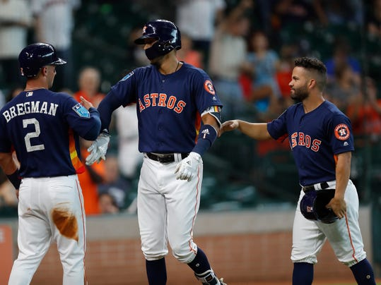 Houston Astros' Carlos Correa, center, celebrates his grand slam with Alex Bregman (2) and Jose Altuve (27) during the first inning of a spring training baseball exhibition game against the Milwaukee Brewers at Minute Maid Park, Tuesday, March 27, 2018, in Houston. (Godofredo A. Vasquez/Houston Chronicle via AP)