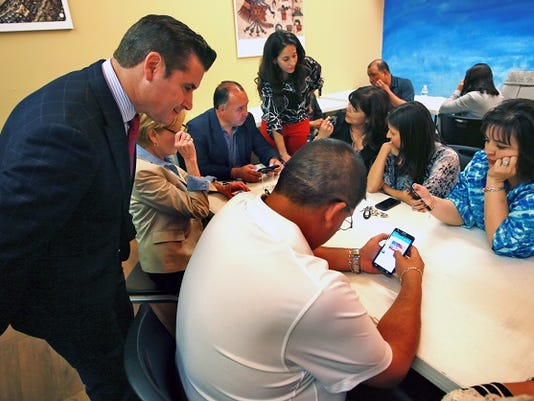 VICTOR CALZADA-EL PASO TIMES Ysleta Independent School District Superintendent Xavier De La Torre, left, checked voting results in Saturday's bond election at a gathering at the Adventures in Learning at 7230 Gateway East.