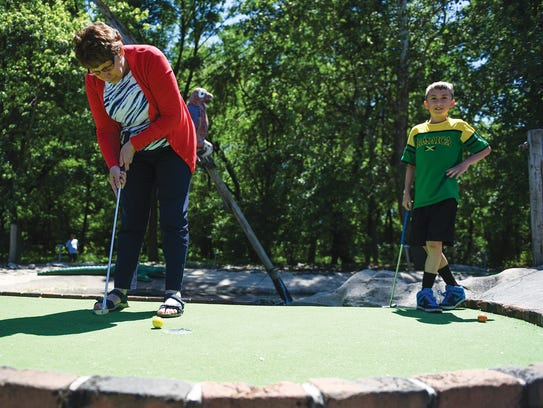 Joyce Weber putts on a hole as her grandkids, Miles