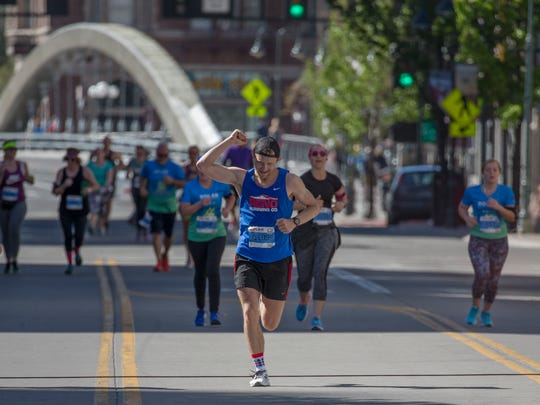 Rob Lugg, the men's marathon winner, celebrates as he heads toward the finish line in the Downtown River Run on Sunday in Reno.