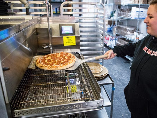 A pepperoni pizza is prepared for a customer at HotBox