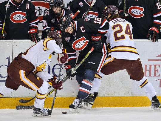 St. Cloud States Ethan Prow (12) gets caught in a sandwich between Minnesota-Duluth defenders.