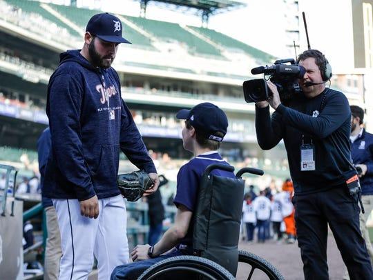 Kyle Van Houten of Hartland, center, meets with pitcher