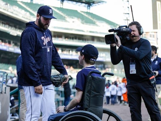 Kyle Van Houten of Hartland, center, meets with pitcher Michael Fulmer by the dugout before a Detroit Tigers game against Kansas City Royals at Comerica Park in Detroit, Friday, April 20, 2018.