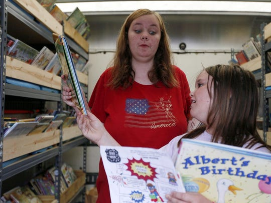 """Shasta John, 13, holds up a book for her sister Shylee, 7, to read while looking at books from the traveling bookmobile from the Burlington Public Library on July 8 at Stone Gardens Apartments in Burlington. """"This book is about a kid going into the second grade and you're going into the second grade,"""" Shasta said to her younger sister."""