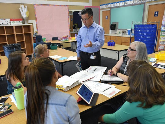 New Booth Elementary School Principal Yuen Fong, standing, talks with a group of first grade teachers planning for the first day of school. The first grade teachers are clockwise Linda Koyen, front left, Meggan Keaps, Tina Novelli, Joan Achley and kathy Tovar.