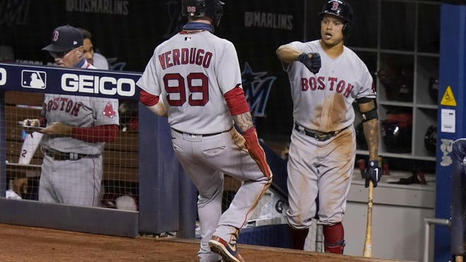 Outfielder Alex Verdugo is congratulated by Yairo Munoz, right, after he scored on a sacrifice fly during Wednesday's game against the Marlins in Miami. Because of injuries, both players were out of the lineup for the Red Sox on Saturday night.